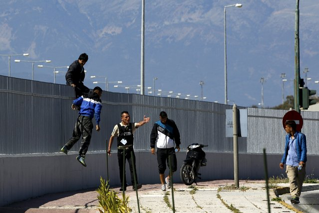 A security officer shouts at Afghan immigrants who have jumped over a fence at a ferry terminal in the western Greek town of Patras May 4, 2015. (Photo by Yannis Behrakis/Reuters)