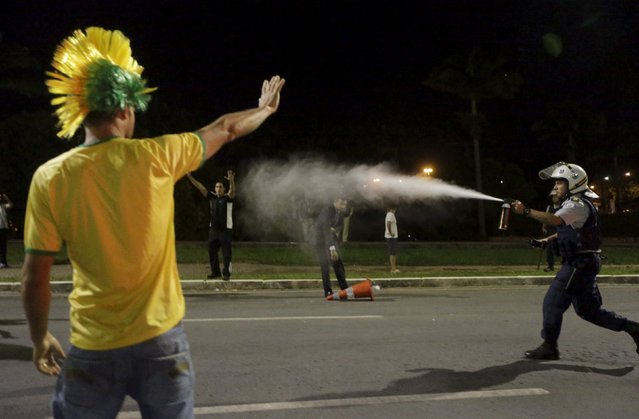 A police officer uses pepper spray during a protest against President Dilma Rousseff's appointment of former President Luiz Inacio Lula da Silva as her chief of staff, in front of the Brazilian national congress in Brasilia, Brazil, March 17, 2016. (Photo by Ricardo Moraes/Reuters)