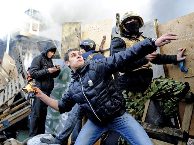 Anti-government protester throws Molotov cocktail at the police in Independence Square in Kiev. (Photo by Alexander Koerner/Getty Images)