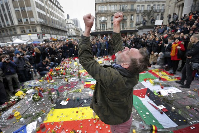 A man reacts at a street memorial following Tuesday's bomb attacks in Brussels, Belgium, March 23, 2016. (Photo by Francois Lenoir/Reuters)
