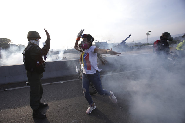 An opponent to Venezuela's President Nicolas Maduro high fives a rebel soldier on a highway overpass outside La Carlota air base amid tear gas fired by loyalist soldiers inside the base in Caracas, Venezuela, Tuesday, April 30, 2019. (Photo by Boris Vergara/AP Photo)