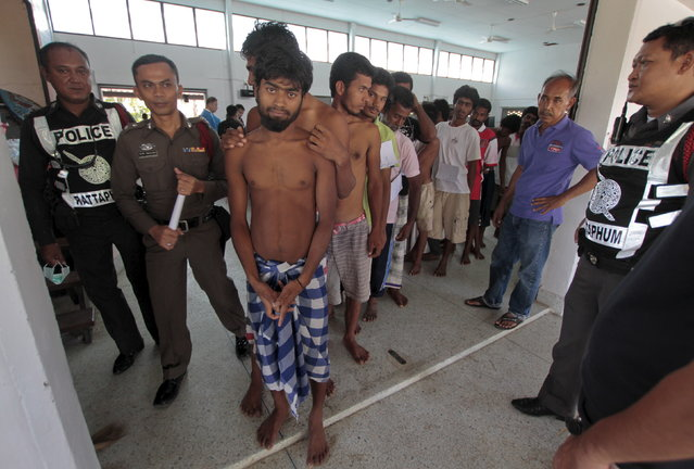 Suspected Rohingya migrants from Myanmar and Bangladesh line up at Rattaphum district hall in Thailand's southern Songkhla province May 9, 2015. (Photo by Surapan Boonthanom/Reuters)