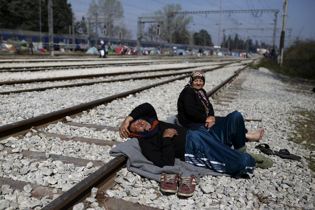 An elderly migrant couple takes a rest at railway tracks at a makeshift camp at the Greek-Macedonian border near the village of Idomeni, Greece, March 28, 2016. (Photo by Marko Djurica/Reuters)