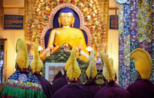 Exile Tibetan Buddhist monks in ceremonial yellow hats of the Gelugpa sect headed by the Dalai Lama conduct ritual prayers at the Tsuglakhang temple on the first day of the Tibetan New Year or Losar in Dharmsala, India, Sunday, March 2, 2014. Tibetans all over the world will mark the arrival of the Wood Horse year with prayers and festivities. (Photo by Ashwini Bhatia/AP Photo)
