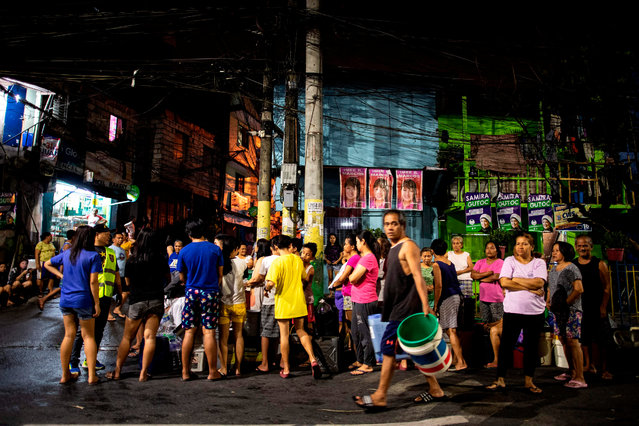 Residents of Addition Hills in Madaluyong City, Manila, queue to recieve water distributed on water tank truck and fire trucks on March 15, 2019. Manila has been hit by its worst water shortage in years, leaving bucket-bearing families to wait hours for a fill up from tanker trucks and some hospitals to turn away less urgent cases. (Photo by Noel Celis/AFP Photo)