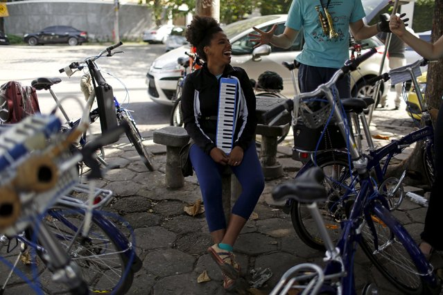 A musician from the Cyclophonica band rests before a ride in Rio de Janeiro May 17, 2015. The Cyclophonica band was formed by a group of musicians riding bicycles around the city, mixing sport and culture and entertaining people on the streets, according to its founder Leonardo Fuks. (Photo by Pilar Olivares/Reuters)