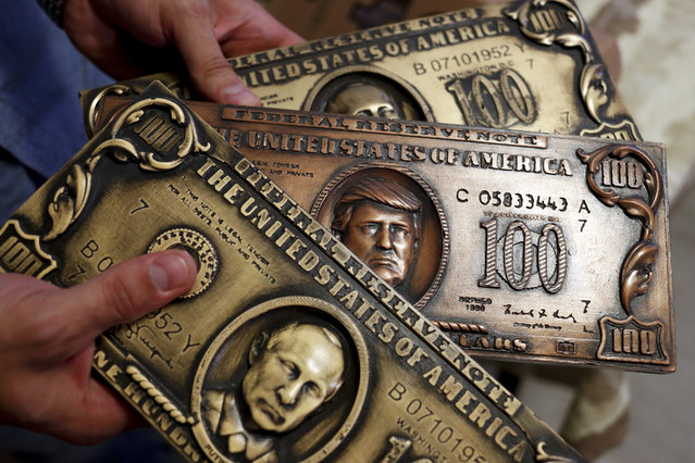 Russian hacker Sergey Pavlovich, better known by his former online alias Police Dog, holds a mock money printing plate with Russian President Vladimir Putin, bottom, and US President Donald Trump, center, faces in place of Benjamin Franklin during an interview with the Associated Press in Moscow, Russia, Wednesday, August 9, 2017. (Photo by Pavel Golovkin/AP Photo)