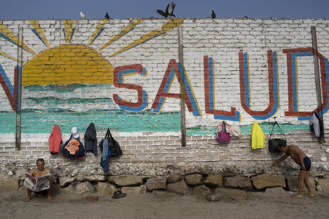 "In this April 25, 2015 photo, a man reads the paper next to a wall decorated with a sun and the Spanish word ""Health"" on Fishermen's Beach, where bathers come for therapeutic swimming in Lima, Peru. Some hug each other and go in as a group, jumping, laughing and running along the shore. Others bathe silently by themselves in the calm, gray sea water. (Photo by Rodrigo Abd/AP Photo)"