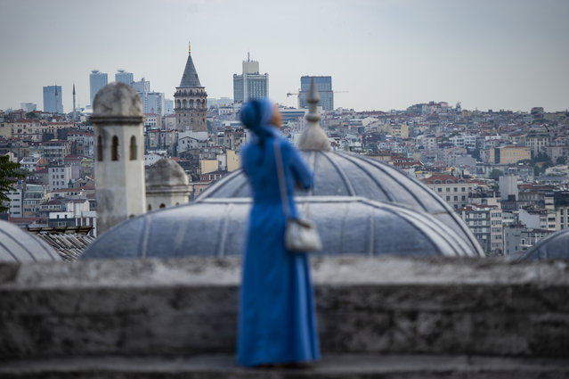 A woman looks on from the terrace of the Suleymaniye mosque after Eid al-Fitr prayers at the Suleymaniye mosque on June 4, 2019 in Istanbul. Muslims throughout the world are marking the month of Ramadan, the holiest month in the Islamic calendar during which devotees fast from dawn till dusk. (Photo by Yasin Akgul/AFP Photo)