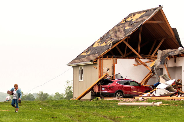 A woman walks away from a damaged house after several tornadoes reportedly touched down, in Linwood, Kansas, U.S., May 29, 2019. (Photo by Nate Chute/Reuters)