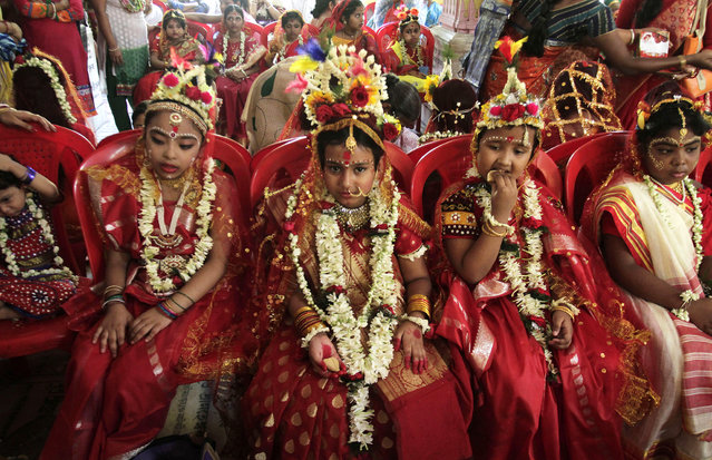 """Young girls yet to attain puberty are dressed up as living goddesses before being worshipped as """"kumari"""" or virgin during the Bengali Hindu festival of Basanti Durga puja performed in the spring in Kolkata, India, Friday, April 15, 2016. Worshipping kumaris or virgins on the ninth day or navami of the festival is an important ritual when they are worshipped as the base power of all creation. The more popular form of Durga festival is performed in autumn when the Hindu mythical figure Rama is said to have called upon goddess Durga to seek her blessings to defeat the evil character Ravana. (Photo by Bikas Das/AP Photo)"""