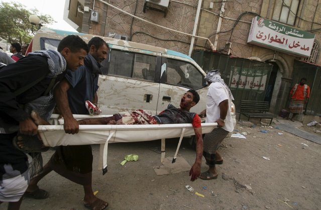 Fighters of the Popular Resistance Committees rush a comrade to a hospital after he was injured during clashes with Houthi fighters in Yemen's southwestern city of Taiz June 26, 2015. (Photo by Reuters/Stringer)