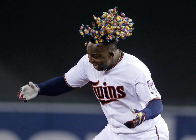 Bubble gum dumped from a bucket falls near the head of Minnesota Twins' Miguel Sano after his walk-off single gave the Twins a 6-5 win over the Cleveland Indians in a baseball game Tuesday, April 26, 2016, in Minneapolis. (Photo by Jim Mone/AP Photo)