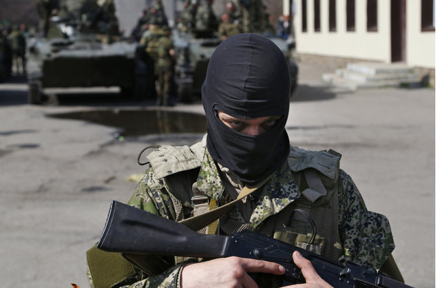 A masked gunman guards combat vehicles with Russian, Donetsk Republic and Ukrainian paratroopers, flags and gunmen on top, parked in downtown of Slovyansk on Wednesday, April 16, 2014. The troops on those vehicles wore green camouflage uniforms, had automatic weapons and grenade launchers and at least one had the St. George ribbon attached to his uniform, which has become a symbol of the pro-Russian insurgency in eastern Ukraine. (Photo by Sergei Grits/AP Photo)