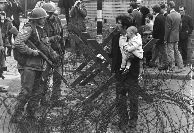 British soldiers stop a man trying to carry his baby through a barbed-wire barricade on the Catholic Falls Road area of Belfast, 1969