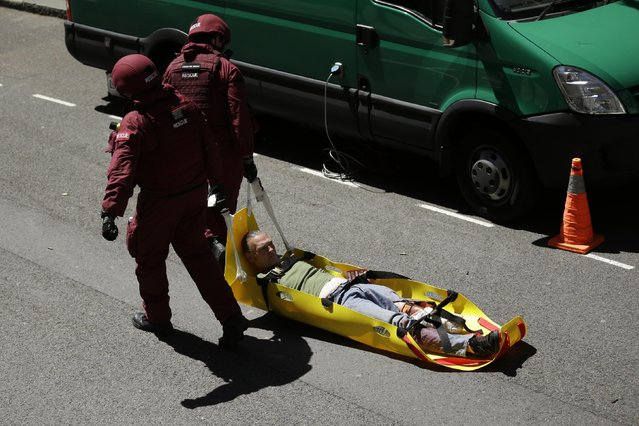During a training exercise for London's emergency services, a casualty is dragged away by rescue officers from the London Fire Brigade, outside the disused Aldwych underground train station in London, Tuesday, June 30, 2015. (Photo by Matt Dunham/AP Photo)