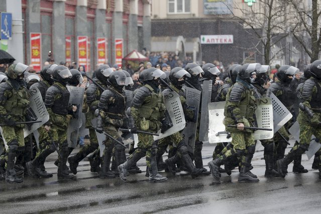 Belarus police walk to block a street during an opposition rally in Minsk, Belarus, Saturday, March 25, 2017. A cordon of club-wielding police blocked the demonstrators' movement along Minsk's main avenue near the Academy of Science. Hulking police detention trucks were deployed in the city center. (Photo by Sergei Grits/AP Photo)