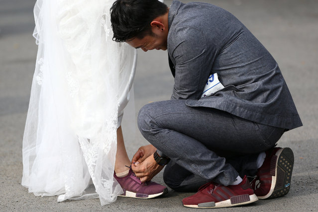 """A man ties the shoe of his fiance as they participate in the """"Running of the Brides"""" race in a park in Bangkok, Thailand March 25, 2017. (Photo by Athit Perawongmetha/Reuters)"""