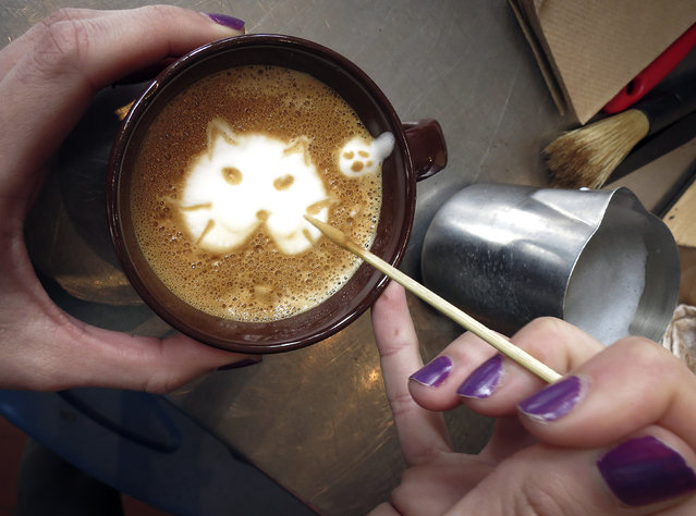 "A worker makes the image of a cat on a ""Cat'achino"" at the cat cafe in New York April 23, 2014. The cat cafe is a pop-up promotional cafe that features cats and beverages in the Bowery section of Manhattan. (Photo by Carlo Allegri/Reuters)"