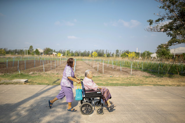 Sampao Jantharun (L), 78, assists Somjit Phuthasiri, 90, on a wheelchair as they head to their home at Wellness Nursing Home Center in Ayutthaya, Thailand, April 9, 2016. (Photo by Athit Perawongmetha/Reuters)
