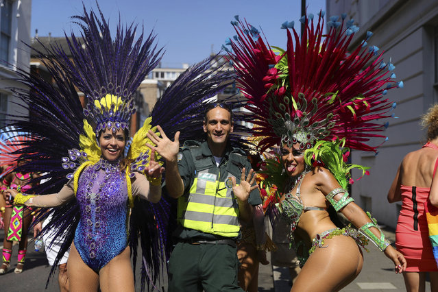 A paramedic joins dancers during the the Notting Hill Carnival in west London, Monday, August 26, 2019. (Photo by Aaron Chown/PA Wire via AP Photo)