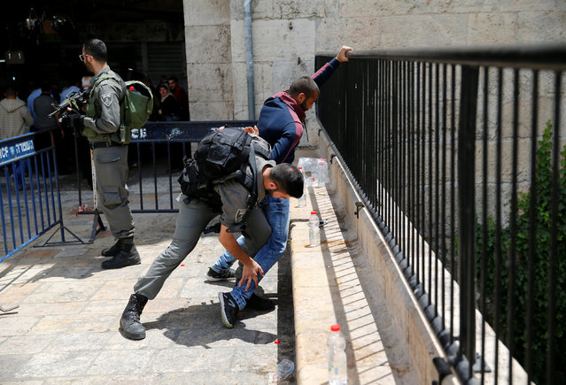 Israeli border policemen perform a body search on a Palestinian man at Damascus Gate in Jerusalem Old City, May 6, 2016. (Photo by Ammar Awad/Reuters)