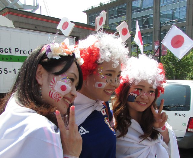 Japanese fans pose for photos before the FIFA Women's World Cup soccer championship between the United States and Japan, in Vancouver, British Columbia, Canada, Sunday, July 5, 2015. (Photo by Anne M. Peterson/AP Photo)