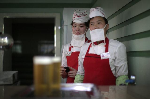 In this Saturday, May 7, 2016, photo, beer servers Kim Yon Hui, 29, left, and Yang Pok Yong, 42, right wait to serve customers at the Taedonggang Beer shop in Pyongyang, North Korea. (Photo by Wong Maye-E/AP Photo)