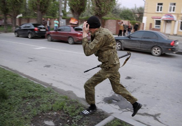 An armed pro-Russian activist runs in Luhansk, eastern Ukraine, May 3, 2014. (Photo by Vasily Fedosenko/Reuters)