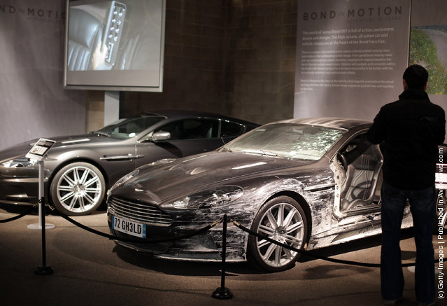 A man looks at the two Aston Martin DBS that were used in the James Bond film Quantum Of Solace and currently being displayed at the Bond In Motion exhibition
