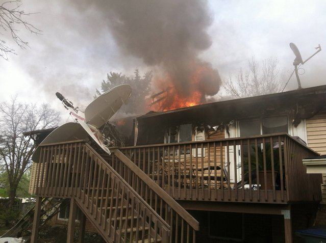 In this photo provided by North Metro Fire Rescue District, a house is on fire after a plane crashes into it, on Monday, May 5, 2014, in Northglenn, Colo. The pilot, Brian Veatch, said that he once owned the home, as indicated by property records, but said he didn't realize that's where he crashed until someone else pointed it out. Veatch tried to put out the fire with a garden hose before he was forced away by burning fuel. (Photo by AP Photo/North Metro Fire Rescue District)