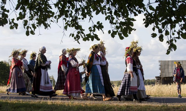 """Belarussian women walk as they take part in the festival of national traditions """"Piatrovski"""" in the village of Shipilovichi, south of Minsk, July 12, 2015. (Photo by Vasily Fedosenko/Reuters)"""