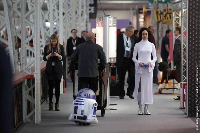 A woman dressed as the Star Wars character Princess Leia drives a radio controlled R2D2 at the 2012 London Toy Fair