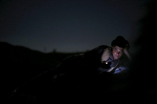 A shepherd checks his mobile phone before going to sleep, as he herds the flock to summer pastures in Serra da Estrela, near Seia, Portugal June 27, 2015. (Photo by Rafael Marchante/Reuters)