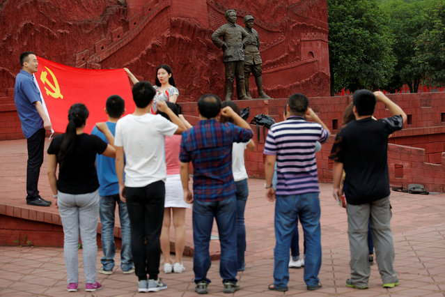 Visitors hold the Chinese national flag as they take a picture next to statues depicting late Chinese chairman Mao Zedong (L) and former general Zhu De during the War of Resistance against Japan, at Jianchuan Museum Cluster in Anren, Sichuan Province, China, May 13, 2016. (Photo by Kim Kyung-Hoon/Reuters)