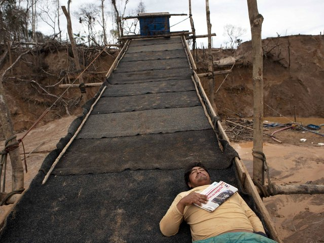 A miner rests on top of a rustic sluice-like contraption layered with pieces of carpets to capture the gold deposits from water sediment in La Pampa in Peru's Madre de Dios region. Engine noise is the characteristic sound of this Amazonian jungle territory. There are no trees, only hills of moved earth and artificial ponds of brown water where gold is mined. (Photo by Rodrigo Abd/AP Photo)