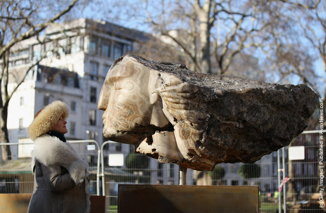 British sculptor Emily Young poses for a photograph with a large stone head she created in Berkeley Square