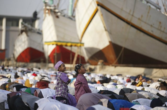 Muslims pray next to traditional Indonesian Phinisi ships on Eid al-Fitr at Sunda Kelapa port in Jakarta, Indonesia July 17, 2015. Indonesia, which has the world's largest Muslim population, celebrates Eid al-Fitr with mass prayers and family visits to mark the end of the holy fasting month of Ramadan. (Photo by Darren Whiteside/Reuters)