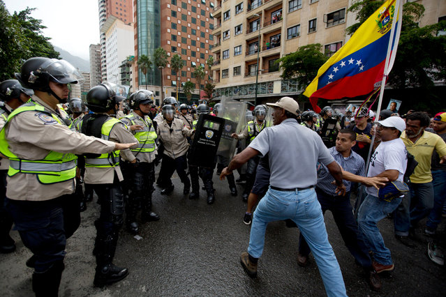 Anti-government demonstrators try to break through a barrier of Bolivarian National Police in an effort to reach the headquarters of the national electoral body, CNE, in Caracas, Venezuela, Wednesday, May 18, 2016. (Photo by Fernando Llano/AP Photo)