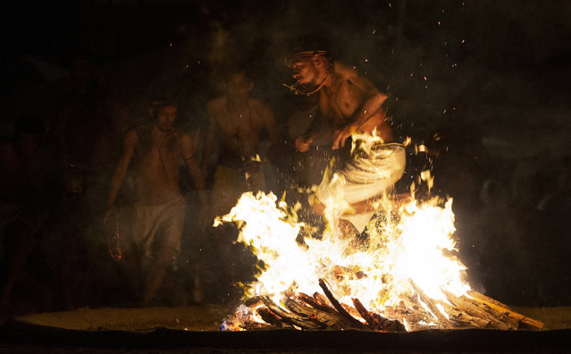 In this photo taken October 11, 2019, a man performs the flame dance on Sorte Mountain where followers of indigenous goddess Maria Lionza gather annually in Venezuela's Yaracuy state. Those immersed in the old tradition say it puts them in a trance that allows them to channel spirits and escape injury from otherwise dangerous feats. (Photo by Ariana Cubillos/AP Photo)