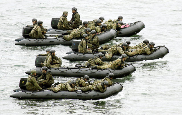 Japan Self-Defense Force (JSDF) soldiers ride rubber boats on the sea approach to Eniyabanare Island during a military drills, off Setouchi town on the southern Japanese island of Amami Oshima, Kagoshima prefecture, in this photo taken by Kyodo May 22, 2014. Japanese troops drifted onto a remote, uninhabited islet on Thursday in drill to simulate the recapture of an island. (Photo by Reuters/Kyodo)