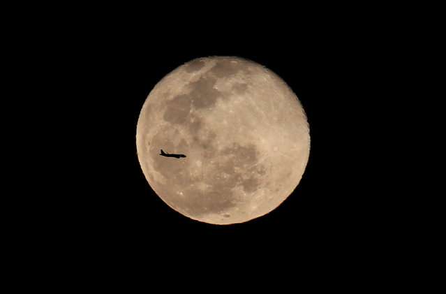A passenger jet flies in front of the moon in Cali, Colombia, May 22, 2016. (Photo by Jaime Saldarriaga/Reuters)