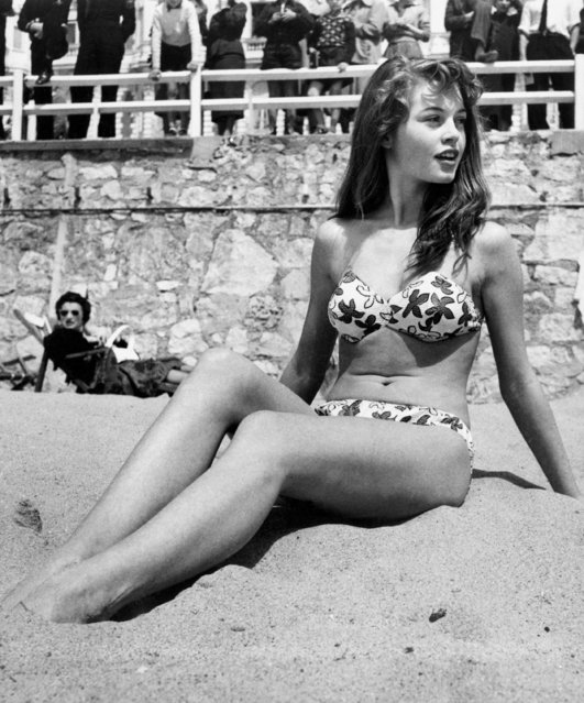 French actress Brigitte Bardot sitting on the beach during the Cannes Film Festival, 1953. (Photo by Patrick Morin/RDA/Getty Images)