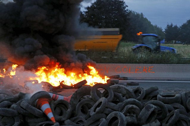A French farmer drives his tractor behind burning tyres to block the A1 Lille-Paris highway early in the morning in Seclin, northern France, July 22, 2015. (Photo by Pascal Rossignol/Reuters)