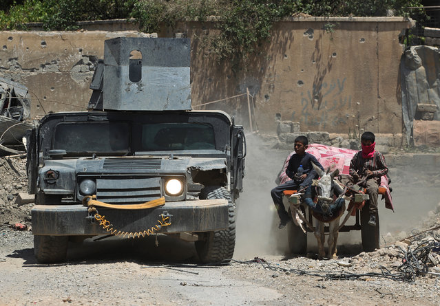 An Iraqi military vehicle passes displaced Iraqi boys returning to their homes in West Mosul's Oreibi neighbourhood after government forces retook control of the area from the Islamic State (IS) group during the ongoing offensive against the jihadists on May 21, 2017. (Photo by Ahmad Al-Rubaye/AFP Photo)