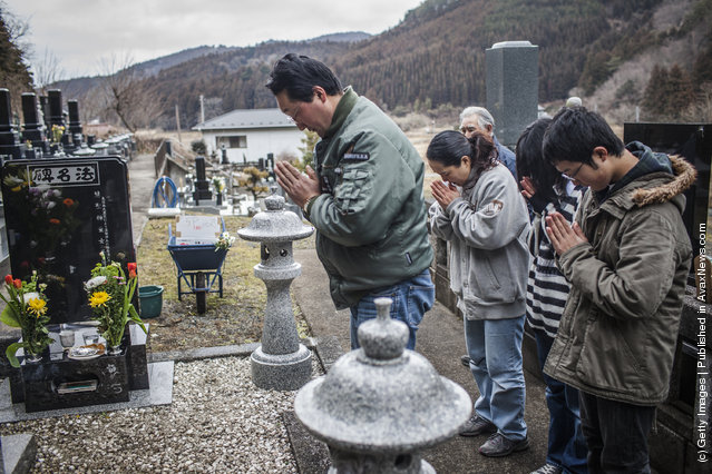 Takahiro Shito, 47, and his wife Sayomi Shito, 46, pray with their children Tomoka, 14, and Kenya 16, and their great uncle Akinori Takahashi, 76, as they pay respects to their daughter Chisato,12, buried in a nearby cemetery, victim of the Okowa Elementary School tragedy, who was killed during last year's tsunami on March 11, 2012 near Ishinomaki, Japan
