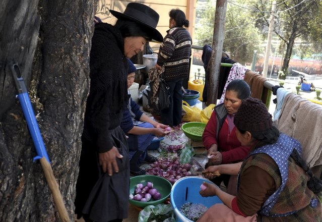Women prepare food for Potosi miners protesting in La Paz, July 27, 2015. For weeks, protesters from the southern Bolivian department of Potosi have called for the construction of hospitals, roads, a cement factory and an international airport to be built in their region as part of a 26-point plan for the government. The striking miners have long called for negotiations to resolve the conflict, putting the onus on President Evo Morales to respond. (Photo by David Mercado/Reuters)