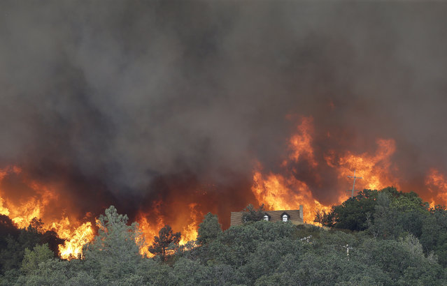 Fire approaches a home near Lower Lake, Calif., Friday, July 31, 2015. (Photo by Jeff Chiu/AP Photo)