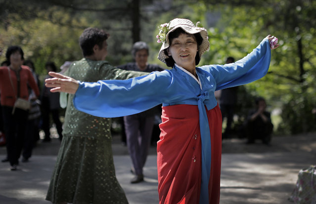 """In this May 10, 2015, photo, Ri Chun Im, 71, poses for a portrait as she dances with other elderly North Korean men and women at a park in Moran Hill in Pyongyang, North Korea. Ri has been dancing everyday for the past 4-5 years. She loves dancing because it keeps her young and healthy. Her motto: """"To live a healthy life devoted to supporting the country's ruling party"""". (Photo by Wong Maye-E/AP Photo)"""