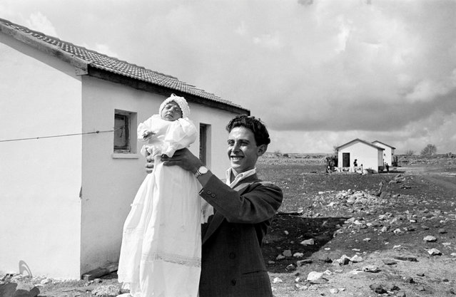 "Israel, 1951. First child born in the settlement of Alma. David Seymour's nephew, Ben Shneiderman, writes: ""The joyous feelings for this first newborn in the settlement of Alma (established by a group of Italian converts to Judaism) in 1951 must have been especially strong in young Israel. Israel was itself a newborn nation, still recovering from the trauma of World War II... The white dress for daughter Miriam echoes the whitewashed new buildings behind her and the billowing clouds above. Viewers of this photo can easily assume that Chim was equally proud of the youthful spirit of Israel"". (Photo by David Seymour/Magnum Photos)"